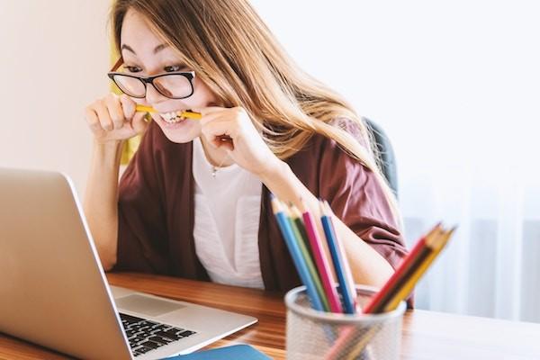 Het meisje op de foto zit achter haar laptop heeft een potlood tussen haar tanden; zij ervaart duidelijk stress.